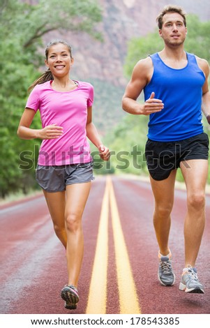 Running people - two runners jogging on road in beautiful nature training for marathon run. Multiracial sports couple, Asian woman sport model and man fitness model exercising together smiling happy. - stock photo