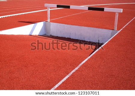 running rack black and white hurdles over water - stock photo