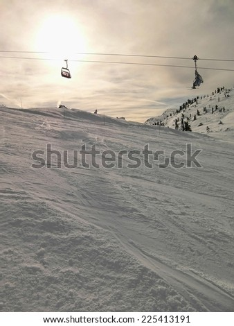 Running rope way above fresh powder snow on slope in ski resort . Evening sun in cloudy sky. - stock photo