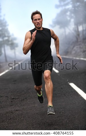 Running runner man sprinting workout on mountain road. Jogging male fitness model working out training for marathon on forest road in amazing nature landscape. - stock photo