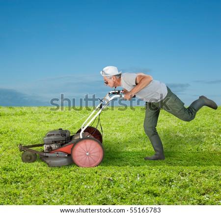 Running senior mowing a green field. - stock photo