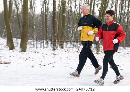 Running seniors in wintertime - stock photo