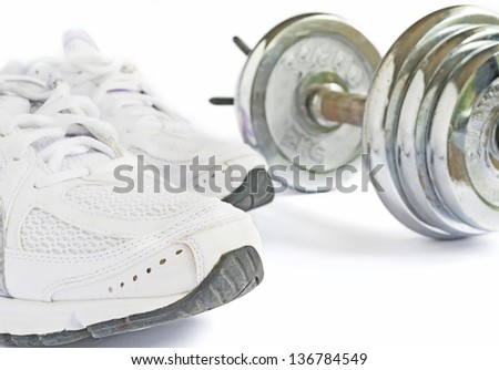running shoes and metal dumbbell on white background - stock photo
