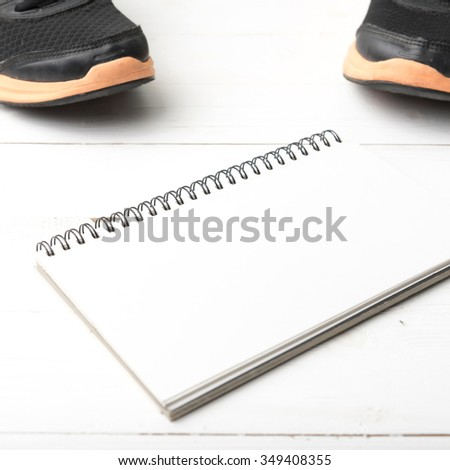 running shoes and notepad on white wood table