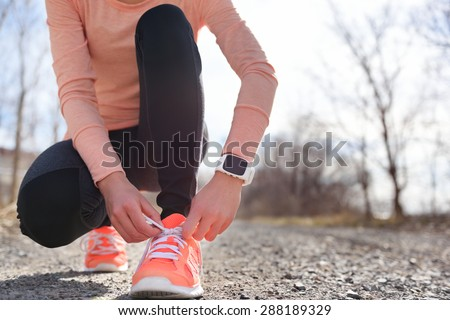 Running shoes and runner sports smartwatch. Female runner tying shoe laces on running trail using smart watch heart rate monitor. - stock photo