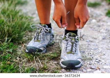 Running shoes being tied by woman getting ready for jogging. Closeup. Shallow depth of field, focus on hands. - stock photo