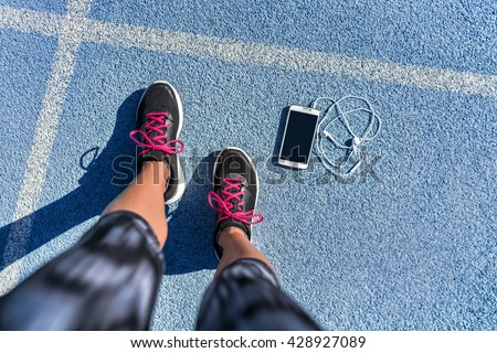 Running shoes girl feet selfie on blue track lane getting ready to run with smartphone and earbuds to listen to mobile phone music app. POV of runner woman athlete and her fit legs in activewear.