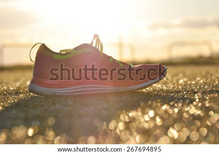 Running shoes in the middle of running oval - stock photo