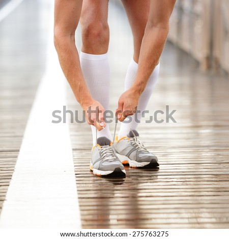 Running shoes. Man tying shoe laces. Closeup of male sport fitness runner getting ready for jogging workout outdoors path in rain in urban city setting. - stock photo