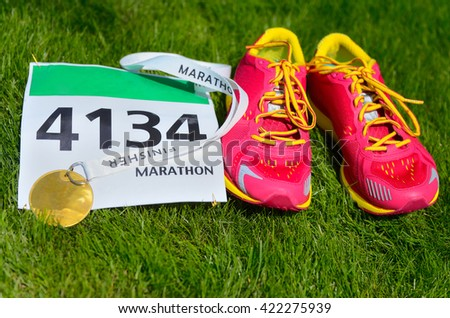 Running shoes,  marathon race bib (number) and finisher medal on grass background, sport, fitness and healthy lifestyle concept  - stock photo