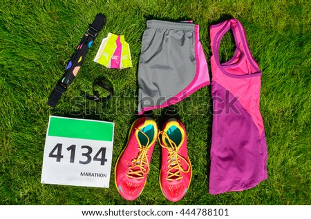 Running shoes, marathon race bib (number), runners gear and energy gels on grass background, sport, fitness and healthy lifestyle concept  - stock photo