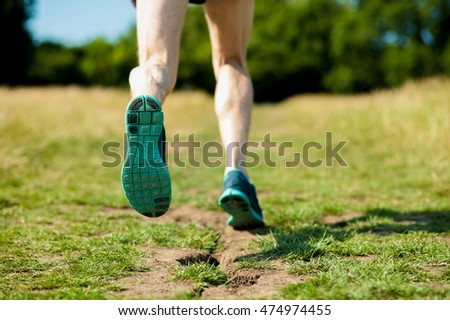 Running shoes of a man jogging cross country outdoor in spring.