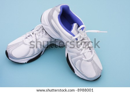 Running shoes on blue background with copy space - stock photo