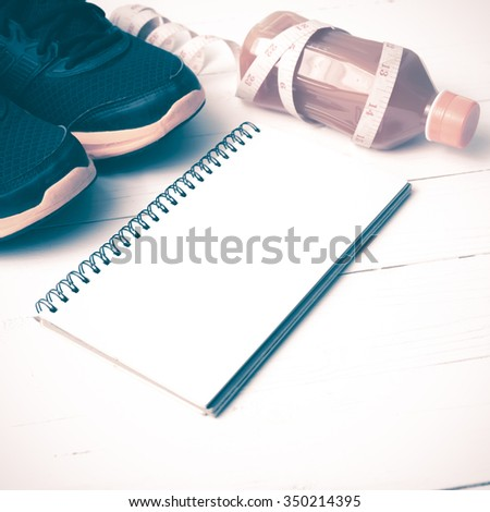 running shoes,orange juice,measuring tape and notepad on white wood background vintage tone color style