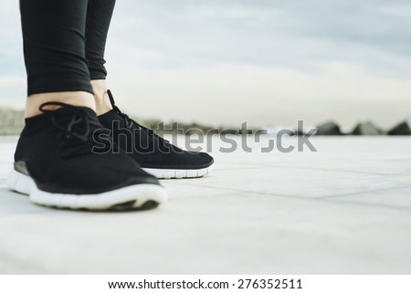 Running shoes. Runner legs and running shoe closeup of man jogging outdoors on road. - stock photo