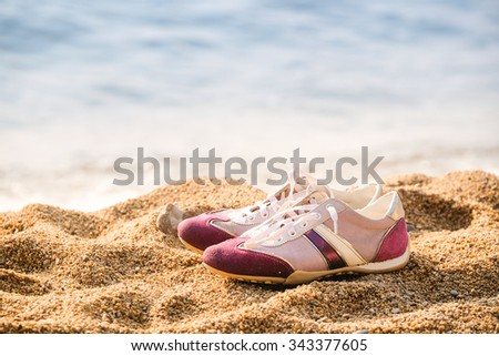 running shoes stand on the beach - stock photo