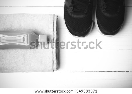 running shoes,towel and orange juice on white wood table black and white tone color style