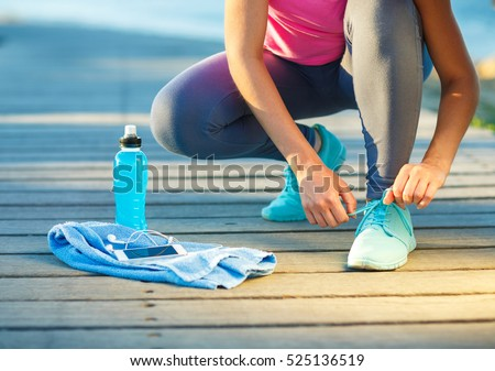 Running shoes - woman tying shoe laces. Closeup of female sport fitness runner getting ready for jogging outdoors on waterfront in late summer or fall