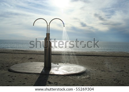 Running shower on the beach, Spain - stock photo