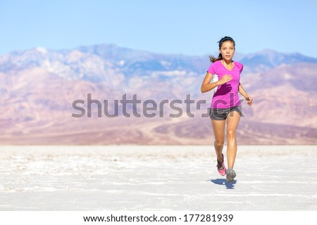 Running sport athlete woman sprinting in trail run in desert. Female fitness runner in sprint workout training in shorts and t-shirt. Fit muscular girl sport model outside under blue sky. - stock photo