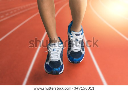 running sport,man runner legs and blue shoes running on the red track in the evening - stock photo