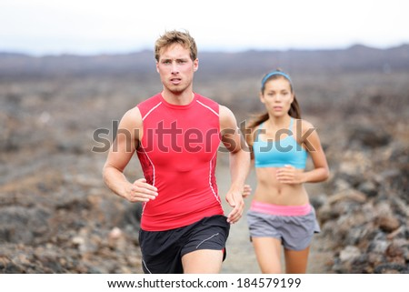 Running sport people jogging on trail in cross country run outdoors training for marathon or triathlon. Fit young fitness model man and asian woman training together outside on Big Island, Hawaii, USA