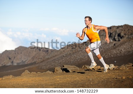 Running sport runner man sprinting in trail run. Fit male fitness sports athlete training sprint in amazing outdoor trail on volcano. Strength and success concept in compression shorts. Full body. - stock photo
