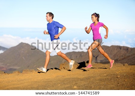 Running sport - Runners couple in trail run outside in amazing nature. Fit young sports multiracial fitness couple training cross country running together. Asian woman, Caucasian man in full body. - stock photo