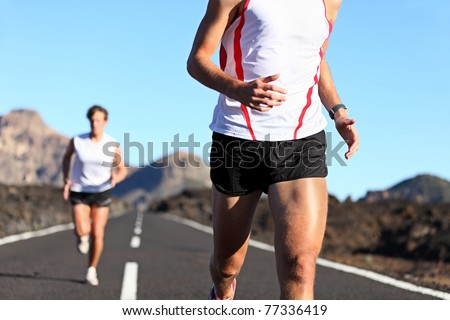 Running Sport. Runners on road in endurance run outdoors in beautiful landscape. closeup of man legs and torso with male runner in the background. Shallow DOF, focus on hips and arm. - stock photo