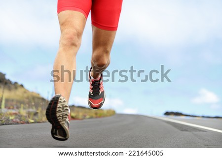 Running sport shoes and legs. Man runner legs and shoes in action on road outdoors at sunset. Male athlete model. - stock photo