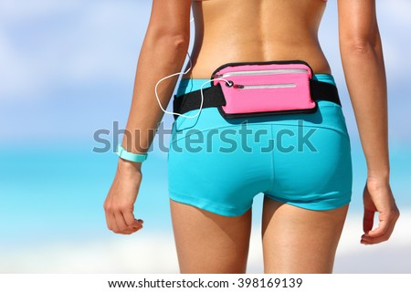 Running sports gear wearable tech female runner wearing fitness smart watch and smartphone holder waist pack for listening to music during outdoor workout. Closeup of shorts and behind. - stock photo