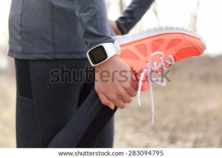 Running stretching - runner wearing smartwatch. Closeup of running shoes, woman stretching leg as warm-up before run with sport activity tracker watch at wrist to monitor the heart rate during cardio. - stock photo