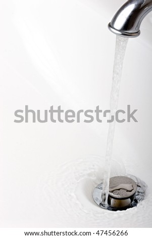 Running tap water into a drain in a sink - stock photo