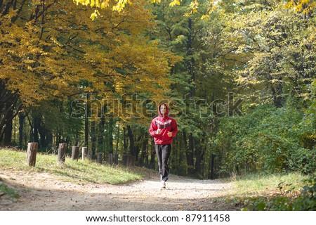 running  the autumn forest - stock photo