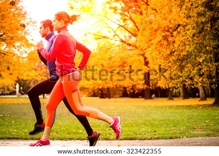 Running together - friends jogging together in park, rear view - stock photo