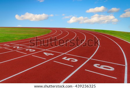 Running track and green grass with blue sky background.