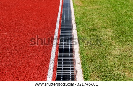 Running track edge with green grass - stock photo