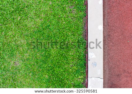 Running track from top view with patch of lawn on the left - stock photo