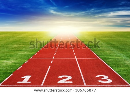Running track through beautiful landscape with sunrise and clouds. - stock photo