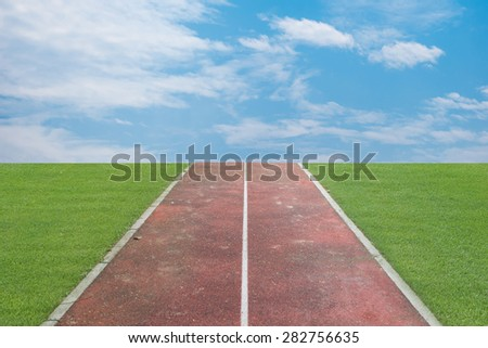 Running track with green grass and blue sky white cloud - stock photo