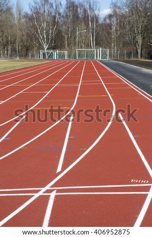 Running tracks. An image of a new running tracks in the sunshine. Grass is about to grow in the football field in the middle of the running track. - stock photo