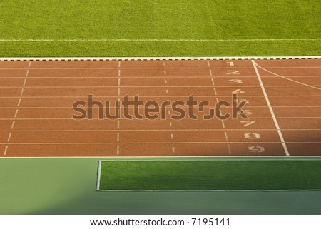 running tracks and green grass in a stadium - stock photo