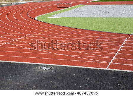 Running tracks on a sunny day. The tracks are recently renewed. Grass is about to grow after a winter period. - stock photo