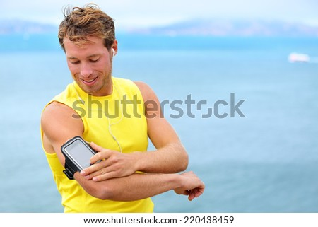 Running training music on smartphone app. Runner man listening to music adjusting settings on armband for smart phone. Fit male fitness model working outdoor by water. - stock photo