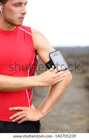 Running training music - runner man listening to music adjusting settings on armband for smartphone. Fit male fitness model working out outside in red sporty outfit. - stock photo