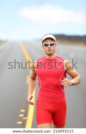 Running triathlon athlete runner man. Male triathlete training for ironman on Hawaii. Young Male athlete running in red compression top on volcano in Kailua-Kona, Big Island, Hawaii. - stock photo