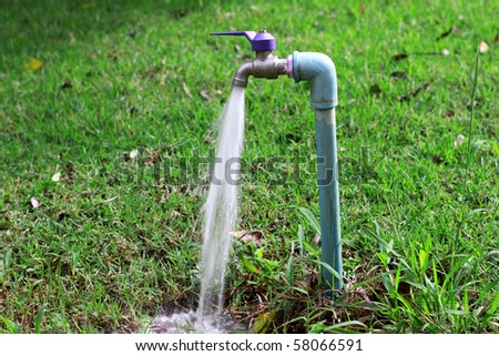 running water from faucet in garden - stock photo