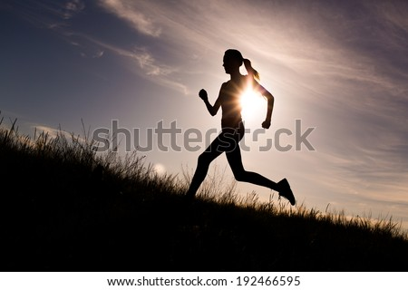 Running woman at beautiful sunset sky. Summer sport and freedom concept. Athlete training on dusk