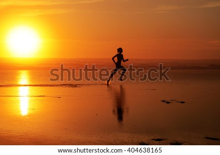 Running woman athlete silhouette at ocean line during sunset (full sun). With feet splashing water & track in the water - stock photo