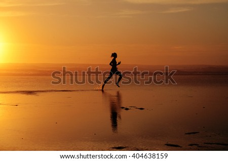 Running woman athlete silhouette at ocean line during sunset (half sun). With feet splashing water & track in the water - stock photo